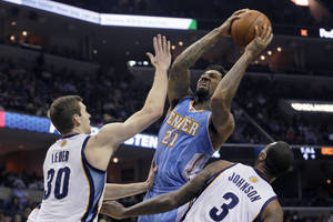 Photo - Denver Nuggets' Wilson Chandler (21) shoots over Memphis Grizzlies' Jon Leuer (30) and James Johnson (3) during the first half of an NBA basketball game in Memphis, Tenn., Saturday, Dec. 28, 2013. (AP Photo/Danny Johnston)