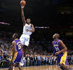 photo - Oklahoma City's Serge Ibaka goes to the basket beside Los Angeles' Metta World Peace and Kobe Bryant, right, during an NBA basketball game between the Oklahoma City Thunder and the Los Angeles Lakers at Chesapeake Energy Arena in Oklahoma City, Tuesday, March 5, 2013. Photo by Bryan Terry, The Oklahoman