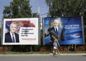 "Photo -   People pass by a billboards showing presidential candidates: pro-Western former Serbian President Boris Tadic, reading: ""For save future"", right, and Tomislav Nikolic, leader of the opposition Serbian Progressive Party (SNS), reading: ""President of all citizens, not of political party"", in Belgrade, Serbia, Saturday, May 12, 2012. Serbian nationalists on Saturday called for nationwide street protests over alleged election fraud, fueling tensions ahead of a presidential runoff vote. Nationalist leader Tomislav Nikolic said his Serbian Progressive Party will start peaceful protests as of Sunday because ""we don't recognize"" parliamentary and local election results held last weekend. (AP Photo/Darko Vojinovic)"