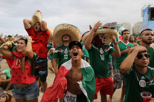 Photo - In this Friday, June 13, 2014 photo, Mexico soccer fan Jose Reyna, center, reacts as he watches his team's World Cup match with Cameroon inside the FIFA Fan Fest area on Copacabana beach in Rio de Janeiro, Brazil. Mexico won 1-0. (AP Photo/Leo Correa)