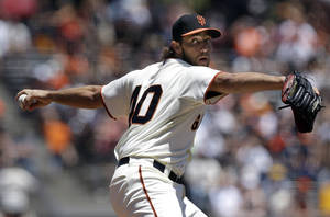 Photo - San Francisco Giants pitcher Madison Bumgarner throws against the Minnesota Twins during the first inning of a baseball game in San Francisco, Sunday, May 25, 2014. (AP Photo/Jeff Chiu)