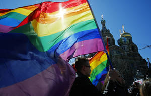 """Photo - FILE - In this Wednesday, May 1, 2013, file photo, gay rights activists carry rainbow flags as they march during a May Day rally in St. Petersburg, Russia. When the Sochi Winter Olympics begin on Friday, Feb. 7, 2014 many will be watching to see whether Russia will enforce its law banning gay """"propaganda"""" among minors if athletes, fans or activists wave rainbow flags or speak out in protest. The message so far has been confusing. (AP Photo/Dmitry Lovetsky, File)"""