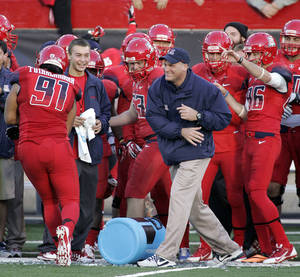 Photo - Arizona head coach Rich Rodriguez, center in blue, celebrates defeating Oregon in the closing seconds of the second half of an NCAA college football game on Saturday, Nov. 23, 2013 in Tucson, Ariz. Arizona won 42 - 16. (AP Photo/John MIller)