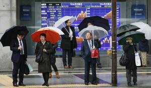 Photo - People stand in front of an electronic stock board of a securities firm in Tokyo, Thursday, March 20, 2014. Asian stocks inched down Thursday after comments from the new head of the Federal Reserve suggested U.S. interest rates could rise sooner than financial markets were anticipating. (AP Photo/Koji Sasahara)