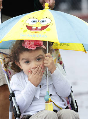 photo - Brooks Beavers, 3, keeps dry under an umbrella Thursday at the fair.