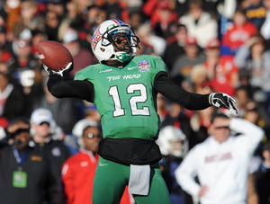 Photo - Marshall's quarterback Rakeem Cato throws in the first half of the Military Bowl NCAA college football game against Maryland, Friday, Dec. 27, 2013 in Annapolis, Md. Marshall won 31-20. Cato was the game MVP. (AP Photo/Gail Burton)