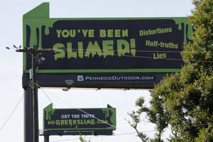 "Photo -   These are billboards along the Pennsylvania Turnpike in New Stanton, Pa., that attack critics of natural gas on Tuesday, Sept. 11, 2012. The website describes critics of gas drilling as ""green slime."" (AP Photo/Gene J. Puskar)"