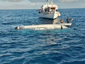 Photo - In this photo released by the Hellenic Coast Guard, local fishermen look a yacht used to transport immigrants illegally that overturned in a fatal accident near the Greek island of Samos, on Monday, May 5, 2014.  At least 22 people drowned in the incident in the eastern Aegean Sea, while 36 were rescued and others remain missing. Coast guard officials recovered the bodies of two women, a man and a boy from the sea, and later found a further 18 bodies, including three children, inside the yacht after it was towed to Samos.(AP Photo/Hellenic Coast Guard)