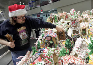 Photo - Chef and GingerBread Lane creator Jon Lovitch repairs one of the gingerbread houses of his annual showpiece, in the New York Hall of Science, in the Queens borough of New York,  Thursday, Dec. 12, 2013. The 1.5-ton, 300-square-foot village that is made entirely of edible gingerbread, royal icing, and candy, has been acknowledged as the largest gingerbread village in the world by the 2014 Guinness World Records. (AP Photo/Richard Drew)