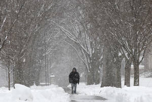 Photo - A pedestrian walks through the campus of Phillips Academy during a winter storm in Andover, Mass. Tuesday, March 19, 2013.  Winter went out with a blast in the Northeast on Tuesday, snow and sleet closing schools in some areas and making roads an icy, slippery mess a day before spring starts. (AP Photo/Winslow Townson)
