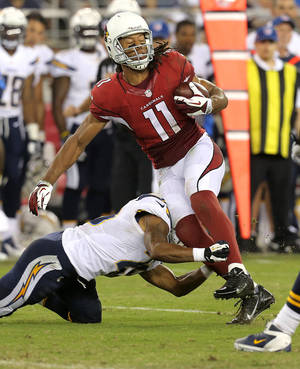 Photo - Arizona Cardinals wide receiver Larry Fitzgerald (11) is tackled against the San Diego Chargers during the first half of a preseason NFL football game, Saturday, Aug. 24, 2013, in Glendale, Ariz. (AP Photo/Rick Scuteri)