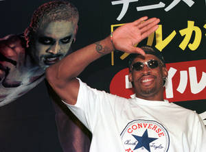 "Photo - FILE - In this July 28, 1997, file photo, former NBA basketball player Dennis Rodman waves to his fans as he arrives at a Tokyo publishing house to promote his autobiography ""Walk on the Wild Side.""  Rodman, one of basketball's most outrageous personalities, has written a book for children. The Hall of Famer's book, ""Dennis The Wild Bull,"" came out Wednesday, Jan. 30, 2013. (AP Photo/Koji Sasahara, File)"