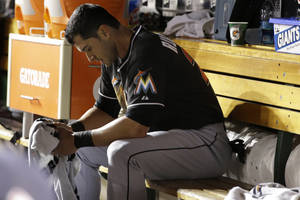 Photo - Miami Marlins Justin Ruggiano sits in the dugout after being put out at second base after attempting to steal third during the sixth inning of a baseball game against the Washington Nationals at Nationals Park in Washington, Thursday, Sept. 19, 2013. (AP Photo/Jacquelyn Martin)