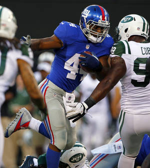 Photo -   New York Giants running back Ahmad Bradshaw (44) runs against New York Jets defensive end Quinton Coples (98) during the first half of a preseason NFL football game on Saturday, Aug. 18, 2012, in East Rutherford, N.J. (AP Photo/Rich Schultz)