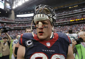 Photo - FILE - In this Sunday, Sept. 29, 2013 file photo, a bloodied Houston Texans' J.J. Watt walks off the field after the team's overtime loss to the Seattle Seahawks in an NFL football game in Houston. Watt's penchant for violent collisions resulted in a deep gash on the bridge of his nose during the game, which required six stitches. The gash kept opening in subsequent games, so now that the season is winding down, Watt tells The Associated Press he'll look into having plastic surgery in the offseason to repair the injury. (AP Photo/David J. Phillip, File)