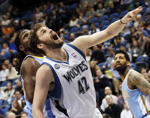 Photo - Minnesota Timberwolves' Kevin Love, right, reacts as he and Denver Nuggets's Kenneth Faried watch Love's shot drop in the first quarter of an NBA basketball game Wednesday, Feb. 12, 2014, in Minneapolis. (AP Photo/Jim Mone)