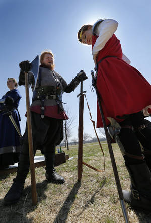 Photo -  David Thompson gives pointers on wearing weapons to Bethany Cavener during a Medieval Fair rehearsal in Reaves Park. The fair opens Friday and continues through Sunday. PHOTO BY STEVE SISNEY, THE OKLAHOMAN  <strong>STEVE SISNEY -   </strong>