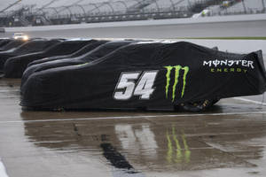 Photo - Covered Sprint cup cars wait out the rain  at Richmond International Raceway in Richmond, Va., Friday, April 25, 2014.  Qualifying for Saturday's Sprint cup race was cancelled.  (AP Photo/Zach Gibson)