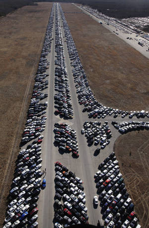 Photo - This Friday, Jan. 18, 2013 aerial photo shows thousands of cars which were damaged in the Oct. 29, 2012 Superstorm Sandy and stored on the runways at Calverton Executive Airpark in Calverton, N.Y. Environmentalists are decrying the placement of the 18,000 damaged automobiles at the defunct defense plant on eastern Long Island near the environmentally protected Pine Barrens. The town supervisor in Riverhead disputes the idea that there is any hazard. The town leased the runways to salvage companies and could reap up to $2.7 million under the lease agreement. (AP Photo/Mark Lennihan)
