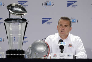 Photo - Ohio State head coach Urban Meyer responds to a question during a news conference for the Big Ten Conference championship NCAA college football game Friday, Dec. 6, 2013, in Indianapolis. Ohio State will play Michigan State, Saturday for the championship. (AP Photo/Darron Cummings)
