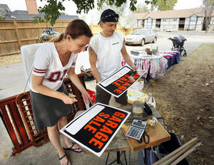 Photo - Above: Kristina Clark and Robert Ortiz make signs for their garage sale, one of many over the weekend as part of Norman's annual citywide garage sale event.