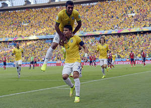 Photo - Brazil's Thiago Silva, bottom, celebrates with Paulinho after scoring the opening goal during the World Cup quarterfinal soccer match between Brazil and Colombia at the Arena Castelao in Fortaleza, Brazil, Friday, July 4, 2014. (AP Photo/Manu Fernandez)