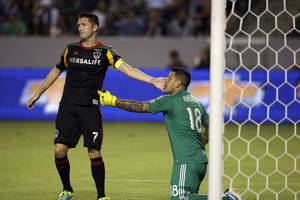 Photo - CORRECTS GOAKEEPER'S NAME TO NICK RIMANDO - Los Angeles Galaxy forward Robbie Keane, left, and goalkeeper Nick Rimando touch in the first half of an MLS soccer game against Real Salt Lake in Carson, Calif., Saturday, Aug. 17, 2013. (AP Photo/Reed Saxon)