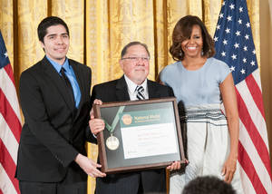 Photo -  Sam Noble Oklahoma Museum of Natural History Director Michael Mares, center, poses for a photograph with Norman community member Ernesto Vargas, left, and First Lady Michelle Obama. The first lady presented the 2014 National Medal for Museum and Library Service to Mares and Vargas, who accepted the award on behalf of the museum at a recent White House ceremony. Photo Provided   <strong></strong>