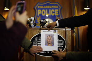 Photo - A photograph of 36-year-old Jason Smith is displayed at a news conference Thursday, Jan. 24, 2013, in Philadelphia. Homicide unit Capt. James Clark says Smith, an exterminator, has been charged with strangling a young Philadelphia doctor found bound and burned in her city row home. (AP Photo/Matt Rourke)