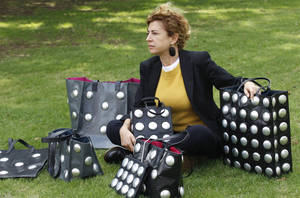 Photo -   This Oct. 24, 2012 photo shows Ilaria Venturini Fendi, a member of the famous fashion family, posing with bags from her Carmina Campus fashion project that produces bags from repurposed materials in Dallas. The bags shown are made of garbage bags and soda cans. (AP Photo/LM Otero)