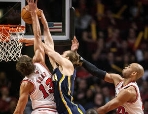 Photo -   Chicago Bulls' Joakim Noah blocks a shot by the Indiana Pacers' Lou Admundson and is called for a foul during the first quarter of an NBA basketball game in Chicago on Monday, March 5, 2012. Bulls' Taj Gibson is at right. (AP Photo/Charles Cherney)