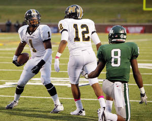 Photo - Ricky Reeves (1) and Cornell Neal (12) of Midwest City react after Reeves intercepted a pass intended for Tre Kelley (8) of Edmond Santa Fe in the second quarter during a high school football game between Midwest City and Edmond Santa Fe at Wantland Stadium in Edmond, Okla., Thursday, Sept. 15, 2011. Photo by Nate Billings, The Oklahoman