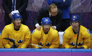 Photo - Sweden coach Par Marts congratulates players, from left, forward Loui Eriksson, Sweden forward Daniel Sedin and forward Nicklas Backstrom after a goal against Slovenia in the third period of a men's ice hockey game at the 2014 Winter Olympics, Wednesday, Feb. 19, 2014, in Sochi, Russia. Sweden won 5-0. (AP Photo/Mark Humphrey)