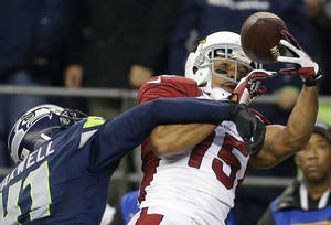 Photo - Arizona Cardinals wide receiver Michael Floyd (15) makes a catch for a touchdown around the defense of Seattle Seahawks cornerback Byron Maxwell, left, in the second half of an NFL football game, Sunday, Dec. 22, 2013, in Seattle. (AP Photo/Elaine Thompson)
