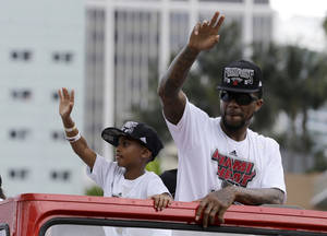 Photo - NBA champion Miami Heat's Udonis Haslem, right,  acknowledges fans during a parade honoring the team in Miami, Monday, June 24, 2013.  (AP Photo/Alan Diaz)