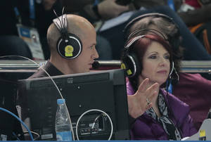"Photo - In this Feb. 13, 2014 photo, figure skating commentator Scott Hamilton speaks with his colleague for NBC television during the men's short program figure skating competition at the 2014 Winter Olympics in Sochi, Russia. Thirty years ago, Hamilton won the figure skating gold medal representing the United States in Sarajevo. Since then, he has pretty much reinvented professional figure skating by creating ""Stars On Ice"" and has been the voice of the sport for decades. (AP Photo/Ivan Sekretarev)"