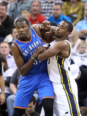 Photo - OKC's Thunder's Kevin Durant, left, battles for position with Utah's Mike Harris during the first half of the Thunder's season-opener in Salt Lake City. The game was still being played at press time. Go to NewsOK.com for game results. AP Photo
