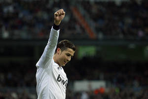 photo - Real Madrid's Cristiano Ronaldo, from Portugal, celebrates Karim Benzema's goal during a Spanish La Liga soccer match against Sevilla at the Santiago Bernabeu stadium in Madrid, Spain, Saturday, Feb. 9, 2013. (AP Photo/Andres Kudacki)
