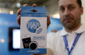 photo - A man holds the Stick-N-Find product at the Mobile World Congress, the world's largest mobile phone trade show, in Barcelona, Spain Wednesday Feb. 27, 2013. Stick-N-Find Technologies, wants to give people a way to find things, by using a new radio technology known as Bluetooth Low Energy, which drastically reduces the power consumption of a transmitting device. (AP Photo/Manu Fernandez)