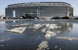 Photo - Snow and slush left from Tuesday's snowfall is seen outside MetLife stadium in East Rutherford, N.J., Wednesday, Dec. 18, 2013. Later Wednesday, at MetLife, officials demonstrated snow removal and melting machinery and outlined emergency weather scenarios and contingency plans for the Super Bowl in February. (AP Photo/Mel Evans)