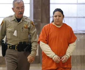 Photo - Marquita Littlebear (right) is led to a courtroom at the Tulsa County Courthouse in Tulsa on Monday, April 21, 2014. MATT BARNARD/Tulsa World