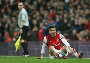 Photo - Arsenal Oliver Giroud lies on the ground following a hard tackle during the English Premier League soccer match between Arsenal and Manchester United at the Emirates stadium in London, Wednesday, Feb. 12, 2014.The game ended 0-0 draw.  (AP Photo/Alastair Grant)