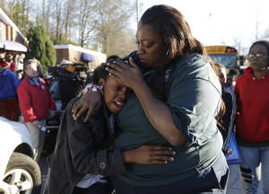 photo - A woman comforts a child after after a shooting at an Price Middle school in Atlanta on Thursday, Jan. 31, 2013. A 14-year-old boy was wounded outside the school Thursday afternoon and a fellow student was in custody as a suspect, authorities said. No other students were hurt. (AP Photo/John Bazemore)