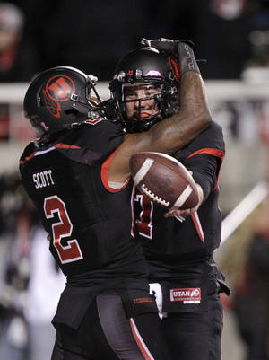 Photo -   Utah quarterback Travis Wilson (7) celebrates with wide receiver Kenneth Scott (2) after scoring on a run in the second quarter during an NCAA college football game against California Saturday, Oct. 27, 2012, in Salt Lake City. (AP Photo/Rick Bowmer)