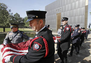 Photo - Oklahoma City police officers and firefighters carry the 911 flag through the memorial to the museum after the Day of Remembrance Ceremony, Tuesday, April 19, 2011.  This was the 16th annual Oklahoma City Bombing Memorial ceremony.   Photo by David McDaniel, The Oklahoman