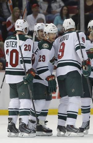 Photo - Minnesota Wilds' Jason Pominville (29) celebrates his goal with teammates Ryan Suter (20), Mikko Koivu (9), of Finland, and Zach Parise (11) during the second period of an NHL hockey game against the Detroit Red Wings Sunday, March 23, 2014 in Detroit. (AP Photo/Duane Burleson)