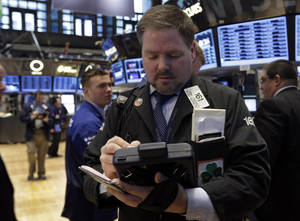Photo - Trader Thomas McCauley, center, works on the floor of the New York Stock Exchange Monday, Feb. 25, 2013. Stocks are opening higher on Wall Street, following the first weekly decline in the S&P 500 index this year. (AP Photo/Richard Drew)