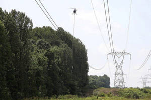 Photo - This July 8, 2013 photo provided by FirstEnergy shows a helicopter aerial saw trimming trees along a FirstEnergy transmission corridor in Doylestown, Ohio. Electric utility tree-trimmers have made their mark on the picturesque hillside where branches coming into contact with high-power lines helped set off a chain-reaction blackout stretching to Canada and the East Coast and fried household appliances 10 years ago. But the sound of chain saws isn't welcome to tree lovers who now see open skies where tall trees once shaded the power lines and the neighborhood. <strong> - AP Photo/HO, FirstEnergy</strong>