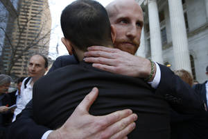 Photo - Plaintiffs challenging Utah's gay marriage ban Derek Kitchen, right, and his partner Moudi Sbeity hug after leaving court following a hearing at the U.S. Circuit Court of Appeals in Denver, Thursday, April 10, 2014. The court is to decide if it agrees with a federal judge in Utah who in mid-December overturned a 2004 voter-passed gay marriage ban, saying it violates gay and lesbian couples' rights to due process and equal protection under the 14th Amendment. (AP Photo/Brennan Linsley)