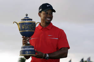 Photo - Tiger Woods holds the Gene Sarazen Cup for winning the Cadillac Championship golf tournament on Sunday, March 10, 2013, in Doral, Fla. (AP Photo/Wilfredo Lee)